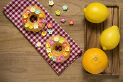 Fancy Doughnuts. Top view of two fancy donuts on wooden table with orange and lemon Stock Photography