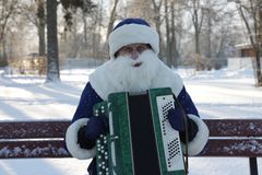 Music, fancy-dress, holiday, winter, Christmas. Man in fancy-dress playing harmonica in winter park, sitting on a bench Royalty Free Stock Images