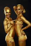Fancy Dress Party. Couple of Women with Golden Metallic Painted Skin. Creativity Stock Photo
