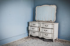 Fancy dresser against a wall. Fancy white dresser against a baby blue wall Royalty Free Stock Photo