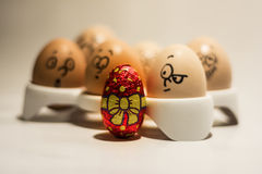 Fancy Easter egg and curious normal eggs Royalty Free Stock Image