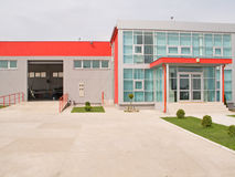 Fancy factory building. With gray walls and red roof Stock Photography