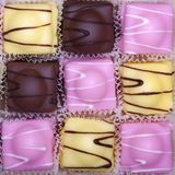Fancy fondant cakes. A checkerboard of fancy fondant cakes in pink, yellow and brown royalty free stock photo
