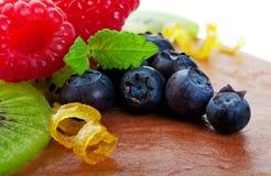 Fancy Garnish Macro. Raspberry, kiwi, blueberry, mint, and delicate lemon curls combine to beautifully garnish a chocolate cheesecake.  Macro Royalty Free Stock Photos