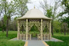 Fancy gazebo in a park. Beautiful gazebo in a park surrounded by trees and grass Royalty Free Stock Photo