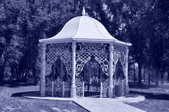 Fancy gazebo in a park. Beautiful gazebo in a park surrounded by trees and grass Stock Image