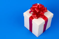 Fancy gift box. White fancy gift box with red ribbon - birthday present concept - isolated on blue background Stock Photos