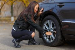 A fancy girl repairs the wheel stock image