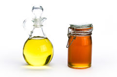 Fancy glass containers of oil and honey. On white isolating background Royalty Free Stock Images