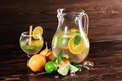 Lime, orange, mint - ingredients for a juice on a table background. A cocktail with rum, liquor and fruits. Copy space. Stock Images