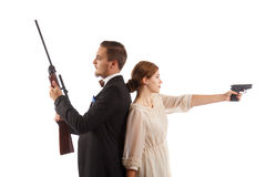 Fancy gun fight. A men in a suit and a girl in a dress both holding guns Stock Image
