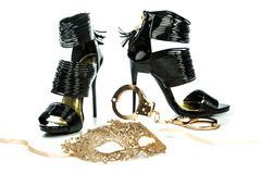 Fancy high heels shoes with golden hand cuffs and mask. Fetish style high heels shoes with ankle straps in shiny black patent leather together with metal hand stock image