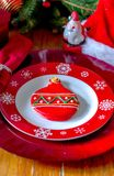 Fancy Christmas  plate setting with pretty sugar cookie. Fancy Holiday plate setting with pretty red iced sugar cookie in the center of a snowflake plate Stock Photography