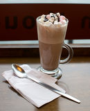 Fancy Hot Chocolate. A tall glass of hot cocoa, with pink and white marshmallows drizzled with chocolate syrup. A long spoon lays next to the glass, ready for Royalty Free Stock Photo