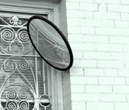 Fancy Ironwork Over Window, White Brick, Round Mirror. Three items compete for attention. The whiteness of the brick on this building, the ornate ironwork over royalty free stock image