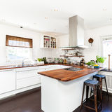 Fancy kitchen interior. Kitchen with wooden counter top and white cupboards Royalty Free Stock Photo