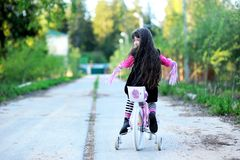 Fancy little girl riding her pink bike. Fancy little girl with long hair riding her pink bike royalty free stock photography