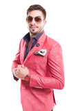 Fancy male model wearing sunglasses and pink elegant jacket. On white background Stock Photography