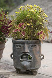 Fancy Mayan planter with face made of clay or stone stock images