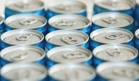 Fancy metal cans with refreshing drinks, in macro picture. Loads of unopened soda or beer cans. Cylindrical metal containers. Canned drinks in a row stock photography