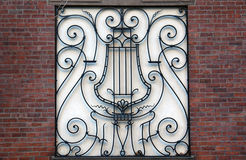 Fancy musical iron work. Fancy musical design inset in wall surrounded by brick Royalty Free Stock Photo