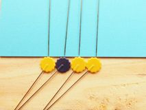 Fancy needle pin. Yellow colors needle pin close up half in turquoise color and wood veneer as a background with natural lights Royalty Free Stock Photography