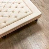 Fancy ottoman on wooden floor Royalty Free Stock Image
