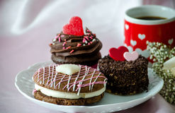 Fancy pastries and a red mug of coffee. Three decadent pastries on a plate. a chocolate whoopee pie, with white filling and pink and white frosting, a chocolate Royalty Free Stock Photo