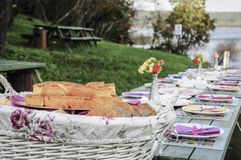 A fancy picnic table full of food by lake in spring. A fancy picnic table full of food by lake in summer Stock Image
