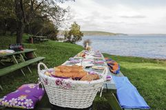 A fancy picnic table full of food by lake in spring. A fancy picnic table full of food by lake in summer Stock Photography