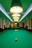 Fancy pool hall. Pool hall with fancy lamps over pool tables, yellow cue and racked balls in foreground Stock Photography