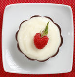 Fancy pudding dessert. Pudding in a black chocolate shell with a fresh raspberry Stock Image