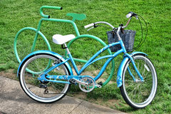 Fancy Retro Bicycle against Cycle Shape Bike Rack. Fancy blue retro style blue bicycle with designer trim leaning against an ornamental cycle shape bike rack in Stock Image