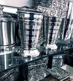 Fancy silver home decor items. Two shelves contain shiny metallic stainless steel crown and sterling silver decorative items for the home, including cups Royalty Free Stock Image