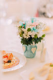 Fancy table setted for a wedding dinner and decorated with flowers in vase Royalty Free Stock Photography