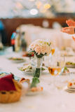 Fancy table setted for a wedding dinner and decorated with flowers in vase Royalty Free Stock Image