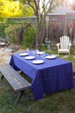 Fancy table setup in a garden. Rustic table with purple cloth and dinner plates in a lush garden Royalty Free Stock Photography