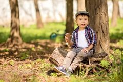 Little child in fancy clothes looking aside with a big ice-cream on a meadow under trees in park or forest. Happy childhood stock image