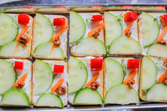 Fancy vegetarian canapes cut in a geometric shapes. Cucumber, carrot and cream cheese crackers with red pepper, pesto and fresh thyme. Modern idea for serving royalty free stock photo
