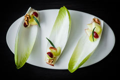 Fancy Waldorf salad on endive leaves served in elegant setting. Waldorf salad on white plate on black table, selective focus on details royalty free stock image