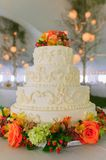 Fancy wedding cake inside a large event tent. Fancy wedding cake with flowers inside a large event tent Stock Photos