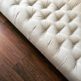 Fancy white ottoman on dark wooden floor Stock Photos