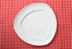 Fancy White Serving Triangle Platter Plate. On red and white checkered background Royalty Free Stock Photography