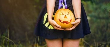 Fancy woman on Halloween in the forest, holding in hands pumpkin with carved face royalty free stock image