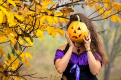 Fancy woman on Halloween in the forest, holding in hands pumpkin with carved face Stock Photography
