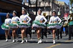 Fanfarekorpsmajorettes synchroniseerden het marcheren van tijdens de jaarlijkse fanfarekorpstentoonstelling ter ere van Patroonhe stock fotografie