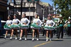 Fanfarekorpsmajorettes synchroniseerden het marcheren van tijdens de jaarlijkse fanfarekorpstentoonstelling ter ere van Patroonhe stock afbeeldingen