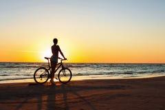 Fangen eines Momentes in der Zeit Sportlicher Frauenradfahrer an Sonnenuntergang backgr Lizenzfreies Stockfoto