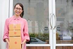 Fangen Sie oben Kleinunternehmer an, Paketkasten am Arbeitsplatz zu halten f lizenzfreie stockfotos