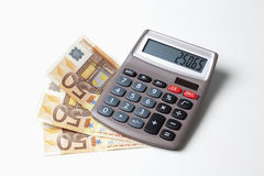 Fanned euro notes and calculator on white background Stock Images